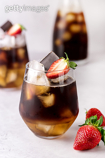 Glasses of Homemade Cold Brew Coffee to Drink for Breakfast Summer Beverage with Ice Cubes Decorated with Strawberry and Chocolate Vertical Close Up