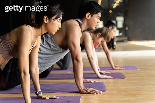Group of Asian women and man doing push-up exercises on yoga mats in aerobics class. Young sporty people working out together on the floor in gym studio.