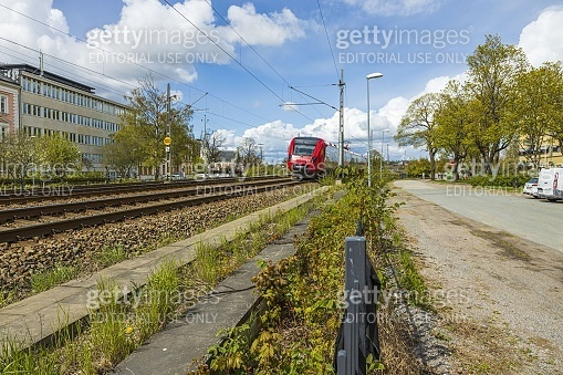 Beautiful city landscape view. Red speed train passing through city. Transportation concept.