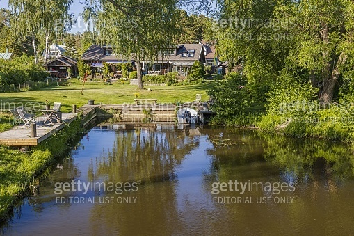 Beautiful natural lake coast landscape view. Quite backwater with boat mooring and place for relaxing. Private houses surrounded of green trees.