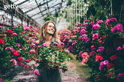 Happy young woman with fresh colorful flowers walks along aromatic blooming plants in modern greenhouse on sunny day.