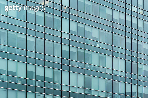 Glass facade texture of a modern office building. High tech architecture. Elements of urban design. Windows of skyscraper tower.