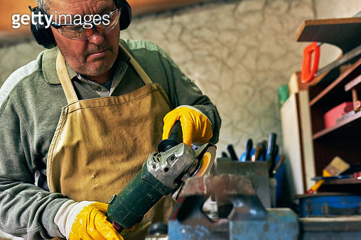Indoor image of adult worker man manufacturing in his workshop. Carpenter male grinding with sparks in repair shop.
