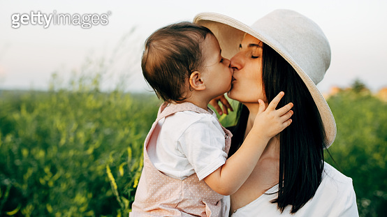 Closeup portrait of pretty mother and cute little girl hug each other outdoor, on the field, on sunset sunlight. Mom and daughter sitting on a field of flowers on nature background.