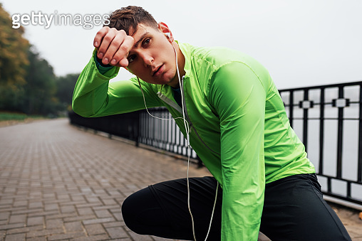 Horizontal image of athletic man stretching outdoor in the morning on the fog nature background. Fitness male exercising in the park and listenting the music on earphones. People and sport