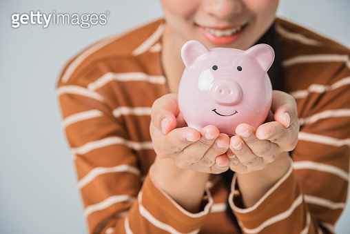 Young asian woman with money coin piggy bank for saving money wealth deposit invest for retirement, happy feeling and smile.