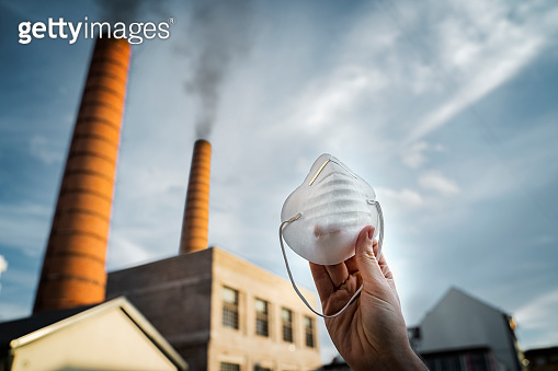Air pollution concept, man holding mask in foreground