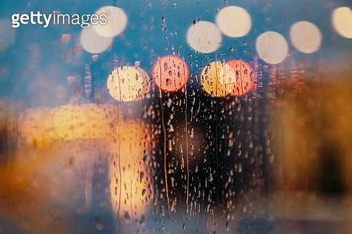 Light of evening city and rain drops on the window. Abstract blurred background