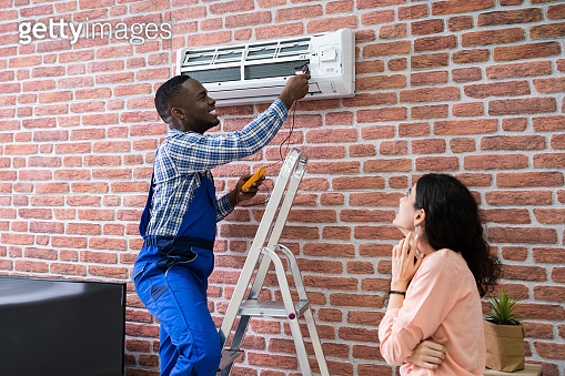 Woman Looking At Technician Repairing Air Conditioner