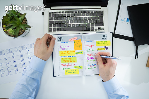 Businessman Making Agenda On Personal Organizer