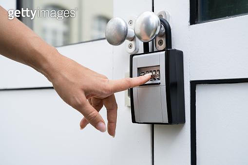 Woman Using Key Safe To Retrieve Keys