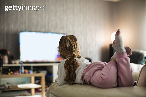 Little girl spending free time in front of the TV
