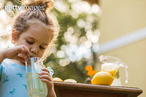 Little girl using a straw to drink a lemonade