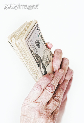 Senior woman's hands holding a wad of American cash money