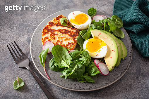 healthy keto paleo diet breakfast: boiled egg, avocado, halloumi cheese, salad leaves