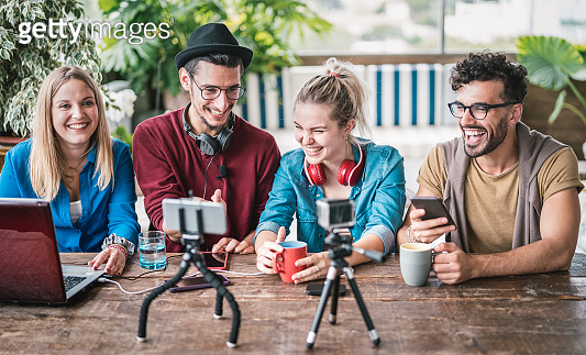 Young friends group sharing info on streaming platform with webcam - Startup marketing concept with millennial guys and girls having fun vlogging live talk feed on social media network - Bright filter