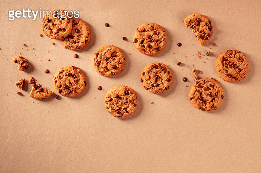 Chocolate chip cookies on a brown paper background, shot from the top with a place for text