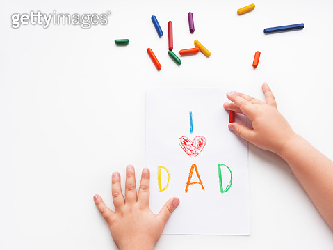 Toddler draws greeting card for Father's day. Kid uses wax crayons to write I Love Dad and to paint red heart symbol. Top view on child's hands and pencils on white background with copy space.