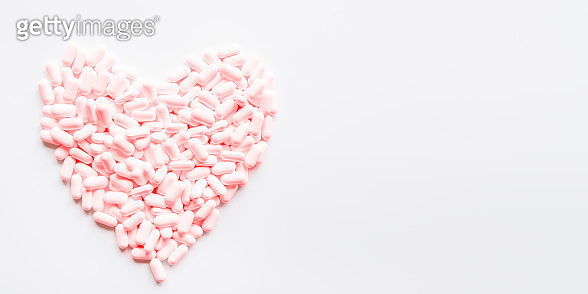Heart made of pink pills. Top view on drugs in shape of heart. Flat lay white background with copy space.