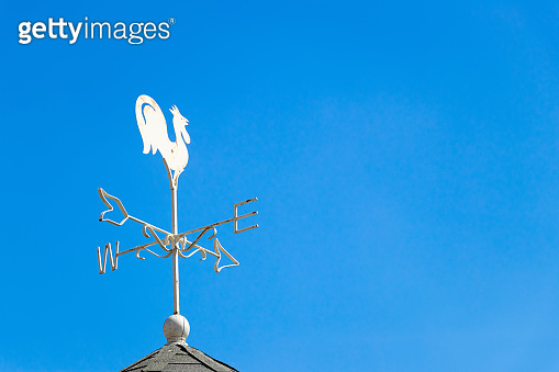 White rooster weather vane show the wind direction on blue sky background