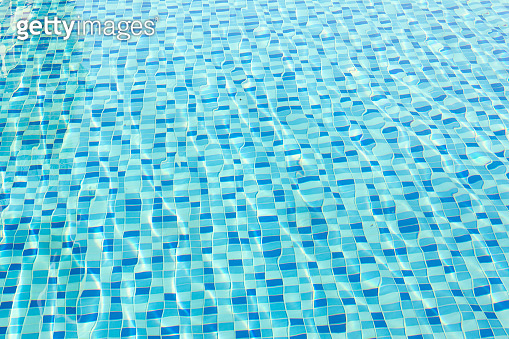 Ripple Water in swimming pool with blue tile floor background
