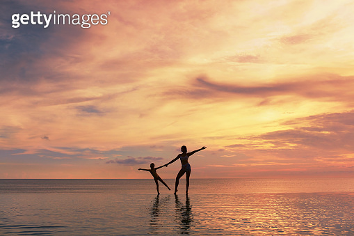 Happy Family. Mother And Kid Silhouettes. Mom And Daughter Posing On Sea Beach. Beautiful Sunset Sky And People Reflection In Water.