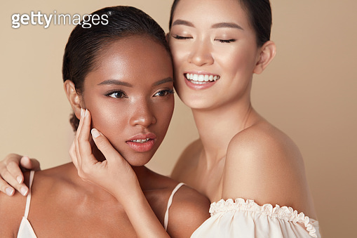 Women. Diversity Models Beauty Portrait. Two Ethnic Female With Nude Makeup And Smooth Hydrated Skin. Smiling Asian Girl Hugs Mixed Race Model And Touches Her Face Against Beige Background.
