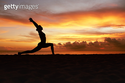 Yoga Poses. Woman Standing In Warrior Pose Asana On Ocean Beach. Female Silhouette Practicing Virabhadrasana At Beautiful Sunset. Yoga As Exercise For Lifestyle.