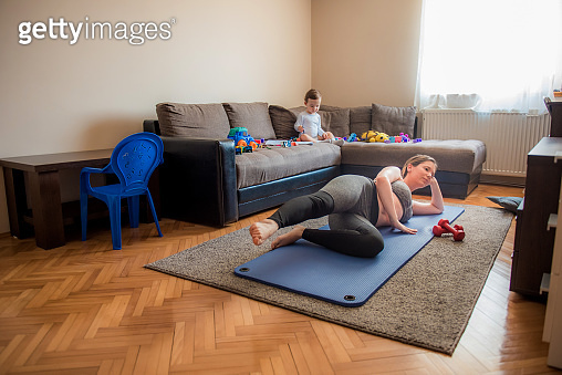 Young mother doing some exercises on a mat while child playing with toys on a sofa