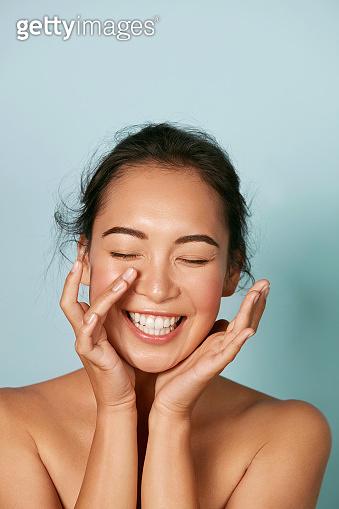 Beauty face. Smiling asian woman touching healthy skin portrait