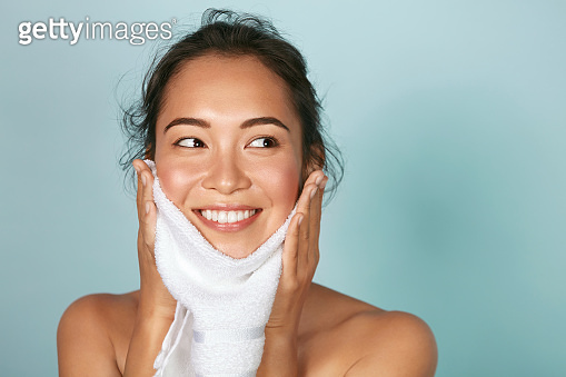 Woman cleaning facial skin with towel after washing face portrait