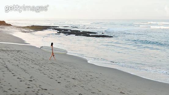 Surfing Girl. Young Woman With White Surfboard Walking On Sandy Beach. Female Going To Surf. Water Sport For Active Lifestyle.