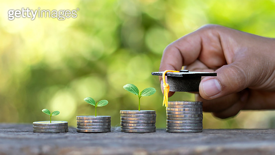 Graduates hats on coins and the hands of people, including the trees growing on the coin. Investment ideas for education