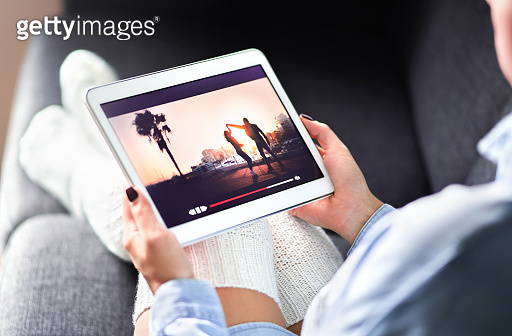 Streaming movie with VOD service. Woman watching online tv series stream. Video on demand app in tablet screen. Television program or film in smart device screen.