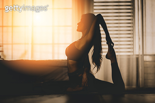 Attractive Asian woman practice yoga king pigeon pose to meditation in bedroom after wake up in the morning Feeling so comfortable and relax,Yoga for Healthcare Concept,Low Key,Warm Tone