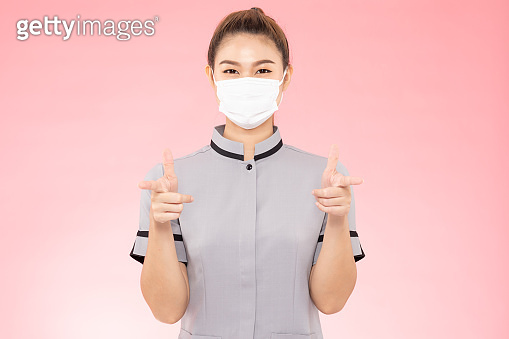 Attractive Beautiful Asian woman maid wearing face mask smile and pointing hand sign feeling so happiness and confident,Isolated on pink background,Cleaning Service concept