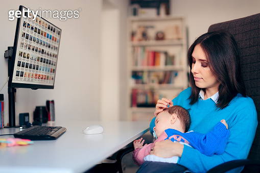 Freelancer Mother Working From Home Holding Baby