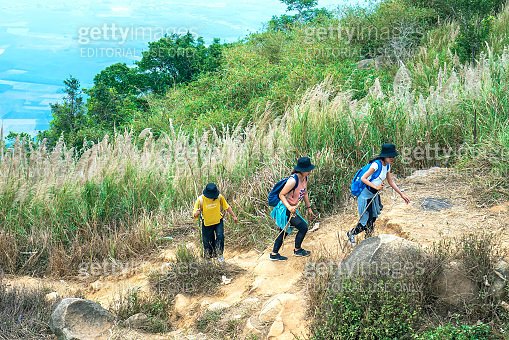 Young girls walking to conquer the highest peak of Ba Den mountain