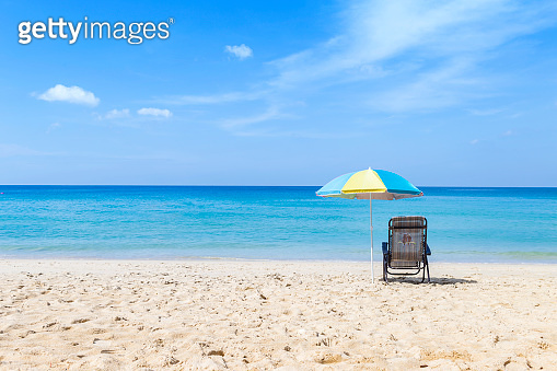 Beach chair under colorful umbrella on beautiful beach look to blue sea and clear blue sky