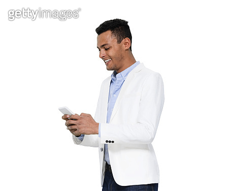 African-american ethnicity male standing in front of white background wearing shirt and using mobile phone