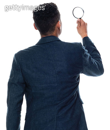 African-american ethnicity young male detective standing in front of white background wearing businesswear and holding magnifying glass