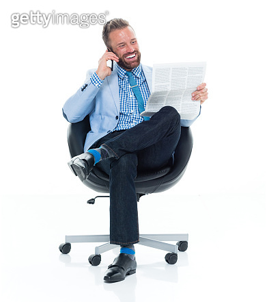 Caucasian male businessman resting in front of white background wearing business casual and holding contract and using smart phone