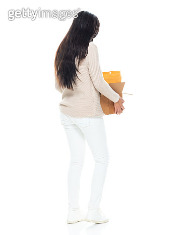 Latin american and hispanic ethnicity female standing in front of white background wearing sweater and holding box