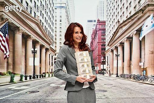 Latin american and hispanic ethnicity female business person standing wearing businesswear and holding us currency