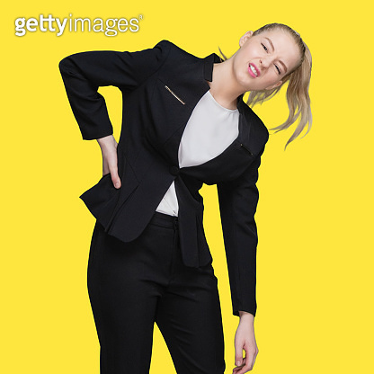Caucasian female businesswoman standing in front of yellow background wearing businesswear