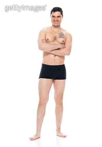 Caucasian male standing in front of white background wearing boxer shorts