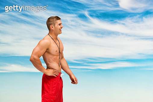 Male lifeguard rescuing who is outdoors wearing shorts and holding life belt