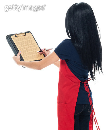 Latin american and hispanic ethnicity young women standing in front of white background wearing apron and holding paperwork