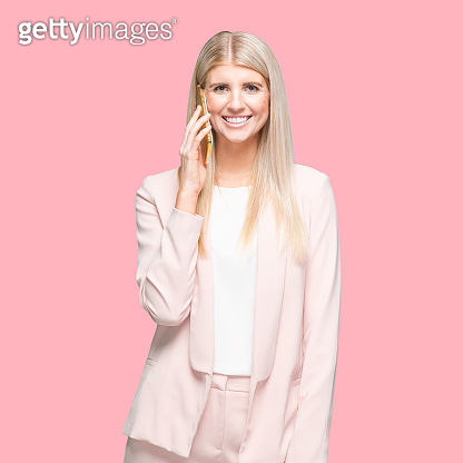 Caucasian female businesswoman standing in front of colored background wearing businesswear and using mobile phone