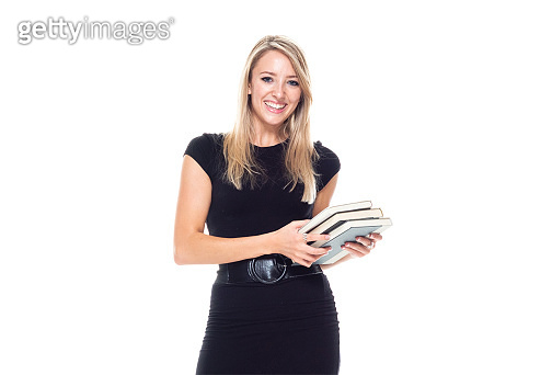 Caucasian female university student standing in front of white background wearing businesswear and holding textbook